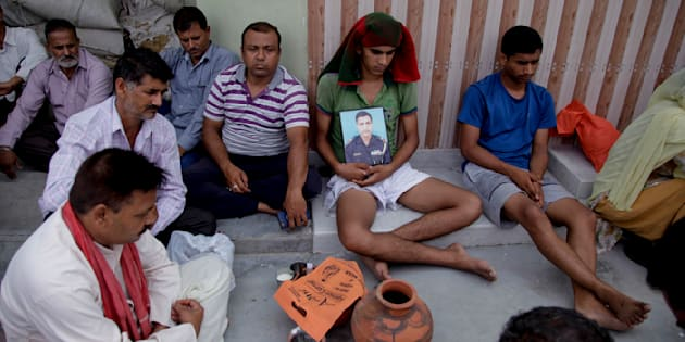 Son of Indian soldier Karnail Singh who was killed in Sunday's militant attack on the Indian army base in Uri, holds his father's portrait, at Shibu Chak village in Bishnah outskirts of Jammu.