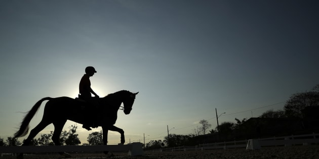 Alex Hua Tian of China works out on his horse at the Olympic Equestrian Center ahead of the 2016 Summer Olympics in Rio de Janeiro, Brazil, Friday, Aug. 5, 2016.