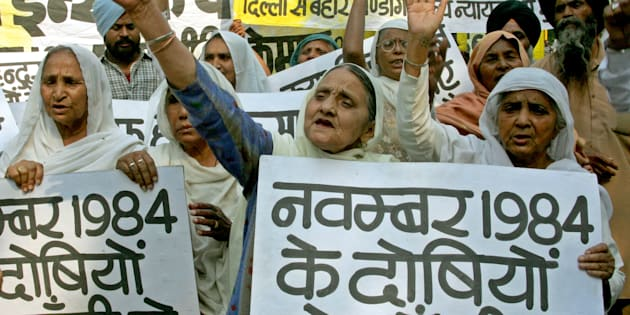 Members of the Sikh community shout slogans while carrying placards during a protest rally in New Delhi, November 5, 2004. The rally demanded punishment of those involved in the riots of 1984, in which more than 2,500 people died, after then Prime Minister Indira Gandhi was shot dead by her Sikh bodyguards. REUTERS/B Mathur