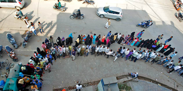 People queue to deposit or exchange their old  high denomination banknotes outside a bank.