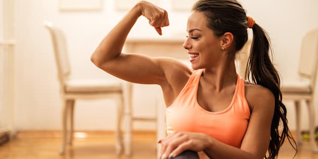 Profile of proud young woman showing off her arm muscles.