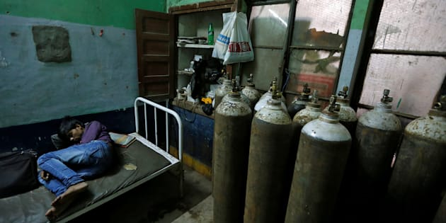 A man sleeps in a room containing oxygen tanks in the Baba Raghav Das hospital in Gorakhpur district, India August 13, 2017. REUTERS/Cathal McNaughton