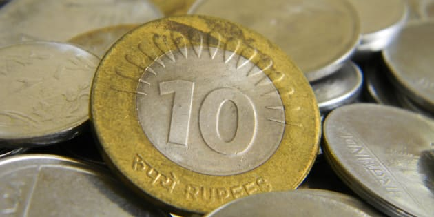 Ten rupee coin of Indian currency lying on top of other coins.