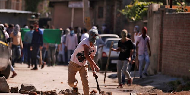 A demonstrator hurls a stone towards Indian police during a protest in Srinagar against the recent killings in Kashmir, July 28, 2016.