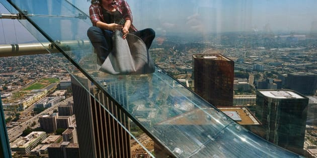 LOS ANGELES, CA - JUNE 25:  A guest rides the SkySlide during the OUE Skyspace LA grand opening block party at OUE Skyspace LA on June 25, 2016 in Los Angeles, California.  (Photo by Mark Davis/Getty Images for Ogilvy PR)
