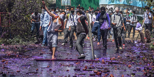 Kashmiri students throw stones at government forces, after they tried to march in the city's main commercial hub, to protest the attack by government forces on students on April 17, 2017 in Srinagar.