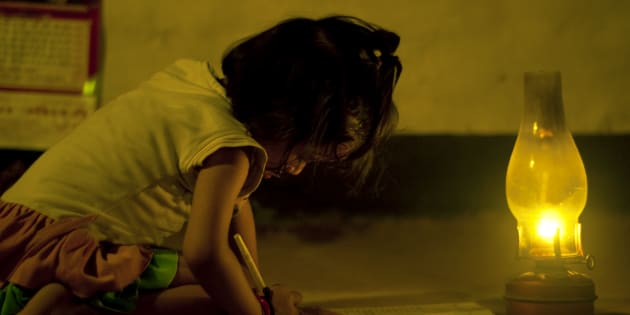 File photo of a girl reading a book by a lamp.