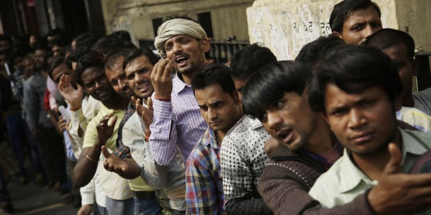 An Indian man gestures to convey that he has no money to buy food, as he stands in a queue with others to deposit and exchange discontinued currency notes outside a bank in New Delhi, India, Saturday, Nov. 12, 2016. Long queues have grown longer, scuffles have broken out and chaotic scenes are being seen across India as millions of people waited to change old currency notes that have become worthless after the government's demonetized high value bills. (AP Photo/Altaf Qadri)