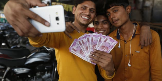 Indians takes selfie with new currency notes of 2000 Indian rupee in Ahmadabad, India, Friday, Nov. 11, 2016. (AP Photo/Ajit Solanki)