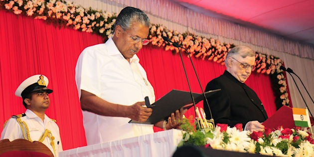 Incoming Chief Minister of Kerala Pinarayi Vijayan (C) stands alongside Governor of Kerala P. Sathasivam (R) as he takes part in a swearing-in ceremony in Thiruvananthapuram on May 25, 2016.