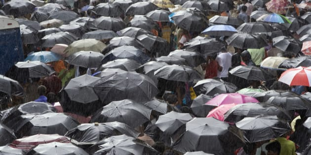 People sheltering under umbrellas during rain, Mumbai, Maharashtra, India