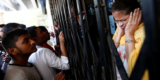 A bank employee reacts as people shout while they wait to enter a bank in Mumbai.