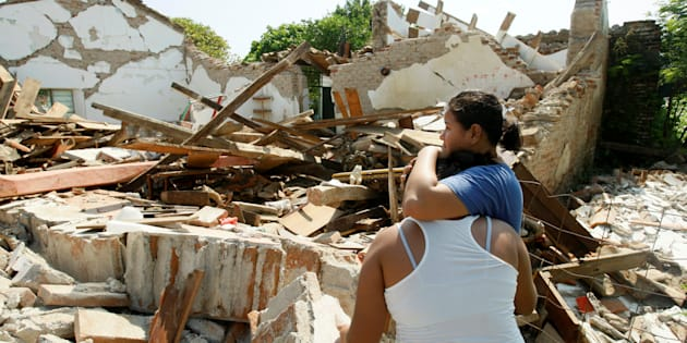 Women hug while standing next to a destroyed house.