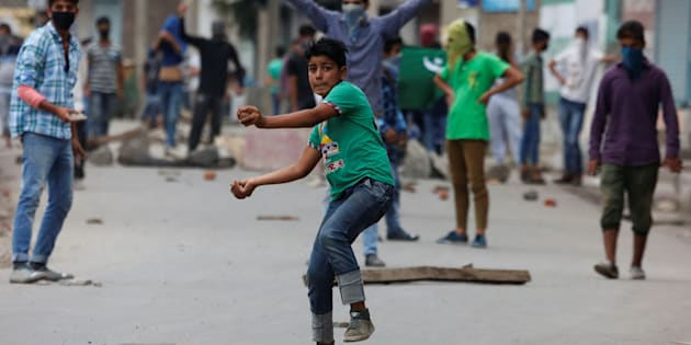 A protester throws stones towards the Indian police during a protest in Srinagar.