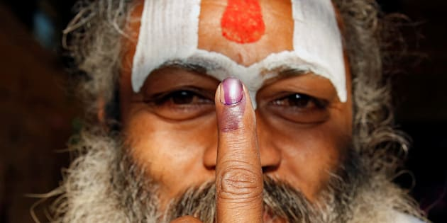 A Sadhu, or Hindu holy man shows his ink marked finger after voting during the state assembly election, in the town of Ayodhya, in Uttar Pradesh.
