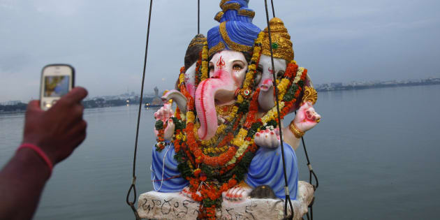 A devotee takes a picture of Hindu god Ganesha as it is lifted to be immersed in the Hussain Sagar Lake during Ganesh Chaturthi festival celebrations.