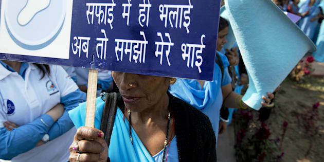 An Indian woman holds a sign reading 'The good only lies in cleanliness, you must understand now my brother'.