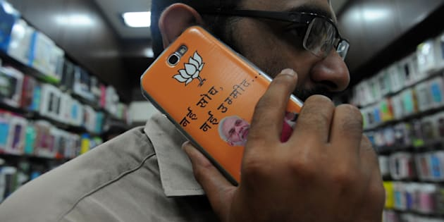 An Indian shopkeeper speaks on his mobile phone adorned with a cover featuring Bharatiya Janata Party's Narendra Modi in Mumbai on April 2, 2014.