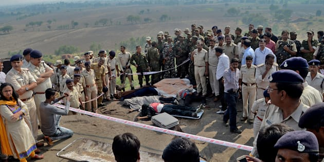 Police officers and Special Task Force soldiers stand beside dead bodies of the suspected members of the banned Students Islamic Movement of India (SIMI), who escaped a high security jail in Bhopal, and later got killed in an encounter at the Acharpura village on the outskirts of Bhopal, India, October 31, 2016.