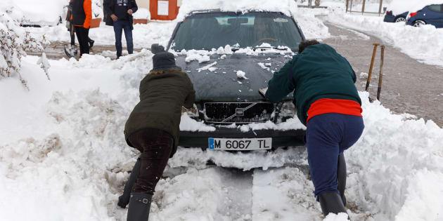 Dos personas rescatan un coche de la nieve en Torrecaballeros, en la provincia de Segovia. CESAR MANSO/AFP/Getty Images