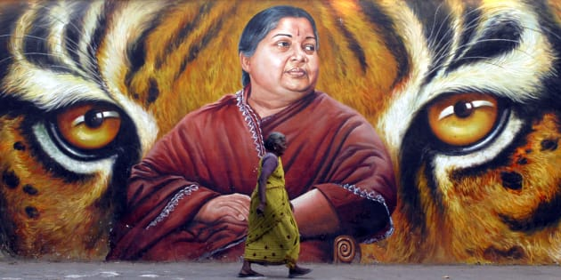 A woman walks in front of a portrait of Jayalalithaa in Chennai in 2009. REUTERS/Babu (INDIA)