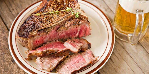 File photo of a thick, partially sliced porterhouse house stake done rare and a glass mug full of ice cold beer.