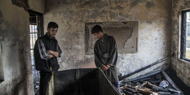 Students inspect the damage of a partially burned government high school in Goripora, on the outskirts of Srinagar.