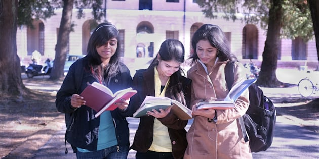 REPRESENTATIVE IMAGE of three college students discussing their notes after exams.