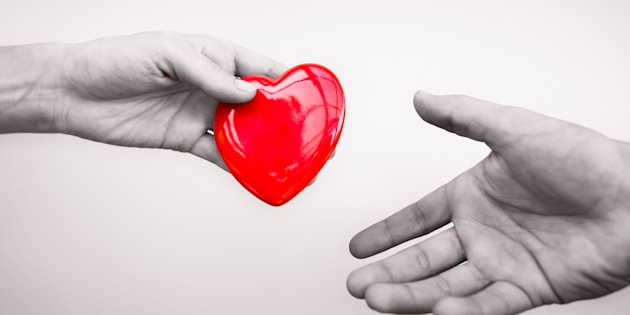Hand giving a heart to another.