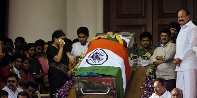 Sasikala Natarajan, left standing, a close friend of India's Tamil Nadu state former Chief Minister Jayaram Jayalalithaa, wipes her tears next to Jayalalithaa's body wrapped in the national flag and kept for public viewing outside an auditorium in Chennai, India, Tuesday, Dec. 6, 2016.
