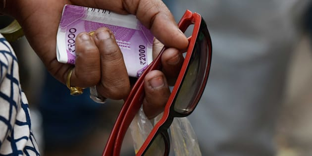 NEW DELHI, INDIA - NOVEMBER 13: A lady holds a 2000 rupee currency as she waits in a long queue to withdraw or deposit their old currency Rs. 500 and 1000 outside a bank at Connaught Place, on November 13, 2016 in New Delhi, India. Tempers frayed as hundreds of thousands of people queued for hours outside banks to swap 500 and 1,000 rupee bank notes after the notes were abolished earlier in the week. Nearly half of India's 2,02,000 ATMs were shut on Friday and those that operated quickly ran out of the new notes as scores of people descended upon them. (Photo by Vipin Kumar/Hindustan Times via Getty Images)