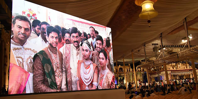 Indian mining tycoon, Gali Janardhan Reddy, (C) is seen on a big screen as he poses with his daughter Bramhani (2R) and son-in-law, Rajeev Reddy (2L) during their wedding at the Bangalore Palace Grounds in Bangalore.