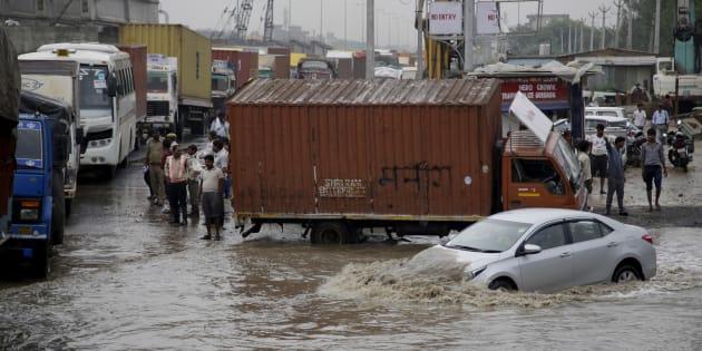 A car navigates its way through a flooded street after heavy rainfall.