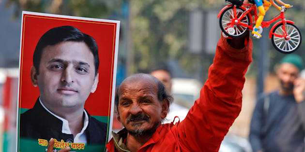A Samajwadi (SP) party worker holds a toy bicycle representing the party's symbol and a poster of chief minister of northern state of Uttar Pradesh Akhilesh Yadav, following the Election Commission's decision to allot the bicycle symbol in Akhilesh's favour, outside the party's headquarters in Lucknow, India, January 17, 2017.