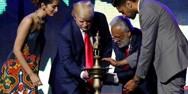 Republican Hindu Coalition Chairman Shalli Kumar (2nd R) helps Republican presidential nominee Donald Trump (2nd L) light a ceremonial diya lamp before he speaks at a Bollywood-themed charity concert put on by the Republican Hindu Coalition in Edison, New Jersey, U.S. October 15, 2016.