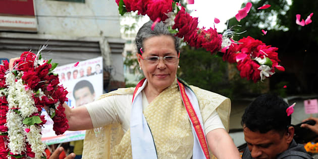 Sonia Gandhi receives floral tributes during the roadshow in Varanasi on August 2, 2016. SANJAY KANOJIA/AFP/Getty Images.
