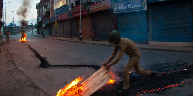 SRINAGAR, KASHMIR, INDIA - JULY 10: Indian government forces douse a burning tire left by the Kashmir protesters in the Ciity center during a curfew after 21 people were killed and more than 400 Injured on July 10, 2016 in Srinagar, the summer capital of Indian Administered Kashmir. The has been more violence in Indian-administered Kashmir after separatist rebel Burhan Wani, 22, was killed in a gunfight with the Indian army on Friday. (Photo by Yawar Nazir/ Getty Images)