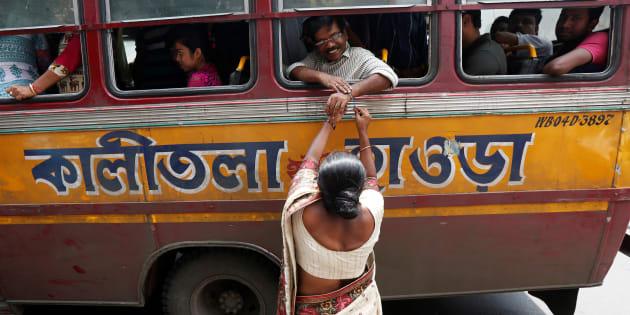 """A woman ties """"Rakhi"""" onto the wrists of a man sitting inside a passenger bus during Raksha Bandhan celebrations in Kolkata."""
