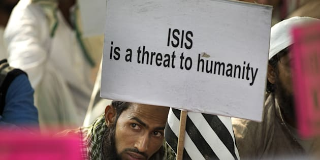 An Indian Muslim man holds a banner during a protest against ISIS in New Delhi, India, Wednesday, Nov. 18, 2015. (AP Photo/Manish Swarup)