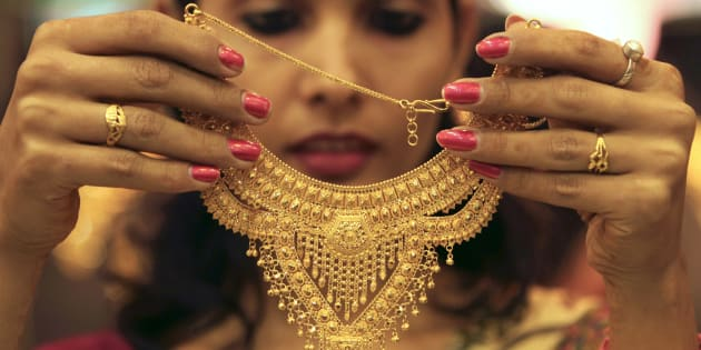 A salesgirl shows a gold necklace to customers at a jewellery showroom in the northern Indian city of Chandigarh November 11, 2012.