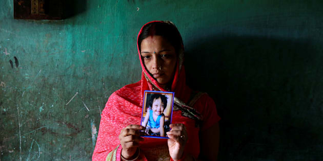 Rinki Singh, 31, holds a photo of her daughter Aarushi, 6, who died in the intensive care unit (ICU) of the Baba Raghav Das hospital in the Gorakhpur district, August 14, 2017.
