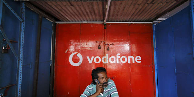 A retail shop owner speaks on his mobile phone outside his closed shop shutters painted with an advertisement for Vodafone at a market in the southern Indian city of Chennai December 30, 2013.  REUTERS/Babu/File photo      TPX IMAGES OF THE DAY