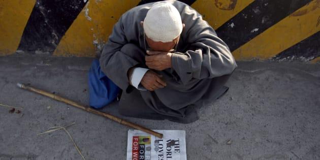 An elderly man sits along a street as he waits for alms in Srinagar August 8, 2007.  REUTERS/Adnan Abidi