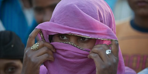 A resident displaced by riots looks on as others speak in the village of Jaula in Muzaffarnagar in 2014. PRAKASH SINGH/AFP/Getty Images