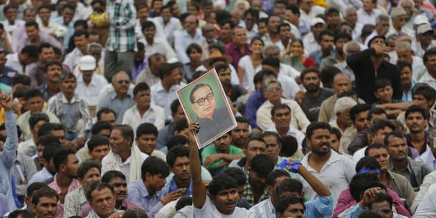 A man displays a portrait of Dalit leader Bhim Rao Ambedkar as hundreds of members of Dalit community gather for a rally in Una.
