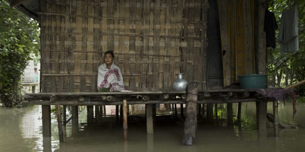 An Indian Mishing tribal woman sits at her traditional hut surrounded by flood waters at Majuli.