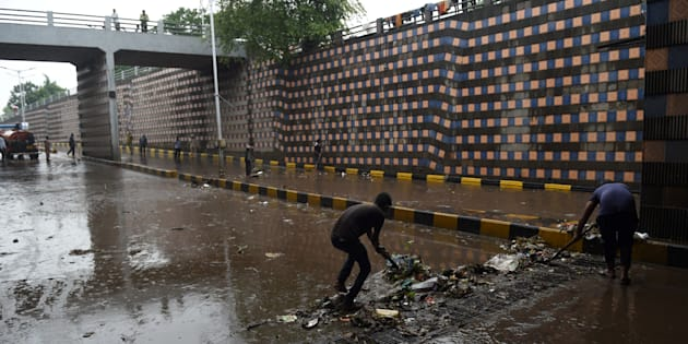 REPRESENTATIVE IMAGE: Indian workers clear blocked drains following heavy rain and flooding in Ahmedabad on July 3, 2017.