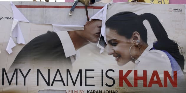 """Supporters of Hindu hardline group Shiv Sena tear a poster of Bollywood actor Shah Rukh Khan's film """"My Name is Khan"""" during a protest in Ahmedabad February 12, 2010."""