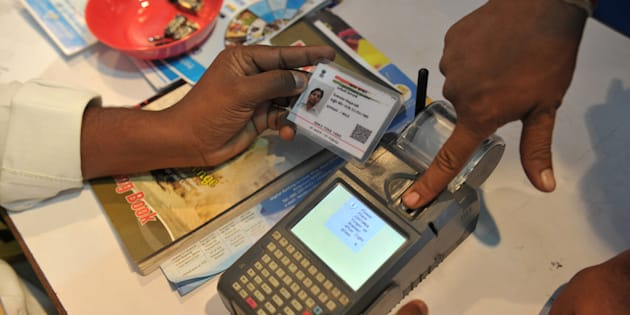 An Indian visitor gives a thumb impression to withdraw money from his bank account with his Aadhaar or Unique Identification (UID) card during a Digi Dhan Mela, held to promote digital payment, in Hyderabad on January 18, 2017.