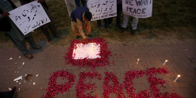 A Christian adjusts a candle next to wording 'Peace' drawn with rose petals during a candlelight vigil for the victims of an overnight attack on the Quetta Police Training Academy, in Islamabad, Pakistan, Tuesday, Oct. 25, 2016.